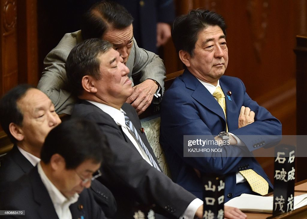 Japan's Prime Minister Shinzo Abe and members of his cabinet attend a lower house plenary session about controversial security bills at the...