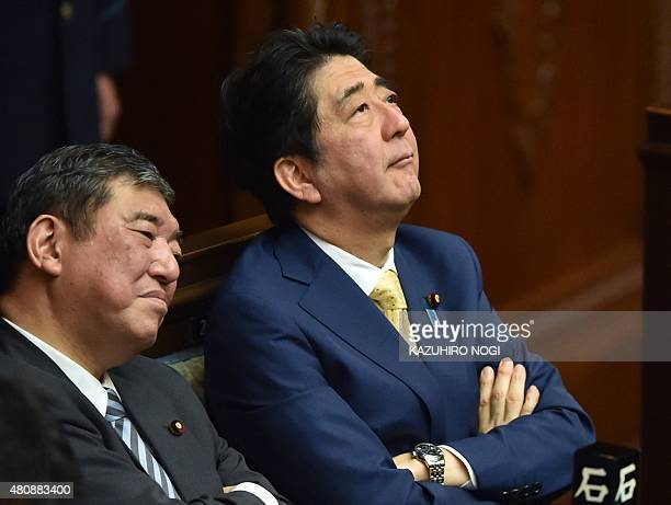 Japan's Prime Minister Shinzo Abe and Regional Revitalization Minister Shigeru Ishiba listen to a speech by a member of an opposition party during a...