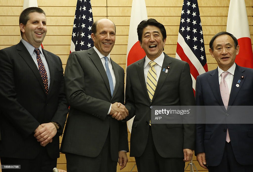 Japan's Prime Minister Shinzo Abe (2nd R) and US ambassador to Japan John Roos (2nd L) exchange smiles with Japan's Chief Cabinet Secretary Yoshihiko Suga (R) and US Assistant Secretary of Defense for Asia and Pacific Secretary Affairs Mark Lippert (L) at their joint announcement on a US-Japan agreement on the return of some of the US bases in Okinawa, at Abe's official residence in Tokyo April 5, 2013. Japan and the United States agreed on a plan that will see some land occupied by the US military returned to the islands in a bid to break the deadlock in a long-stalled deal. AFP PHOTO / POOL / Issei KATO