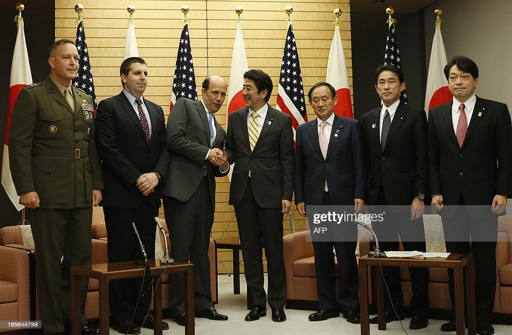 Japan's Prime Minister Shinzo Abe (4th L) and US ambassador to Japan John Roos (3rd L) exchange smiles with Japan's Chief Cabinet Secretary Yoshihiko Suga (3rd R), Japan's Foreign Minister Fumio Kishida (2nd R), Defense Minister Itsunori Onodera (R), US Assistant Secretary of Defense for Asia and Pacific Secretary Affairs <a gi-track='captionPersonalityLinkClicked' href=/galleries/search?phrase=Mark+Lippert&family=editorial&specificpeople=5797334 ng-click='$event.stopPropagation()'>Mark Lippert</a> (2nd R) and Major General Andrew O'Donnell, the US Forces Japan deputy commander, at their joint announcement on a US-Japan agreement on the return of some of the US bases in Okinawa, at Abe's official residence in Tokyo April 5, 2013. Japan and the United States agreed on a plan that will see some land occupied by the US military returned to the islands in a bid to break the deadlock in a long-stalled deal. AFP PHOTO / POOL / Issei KATO