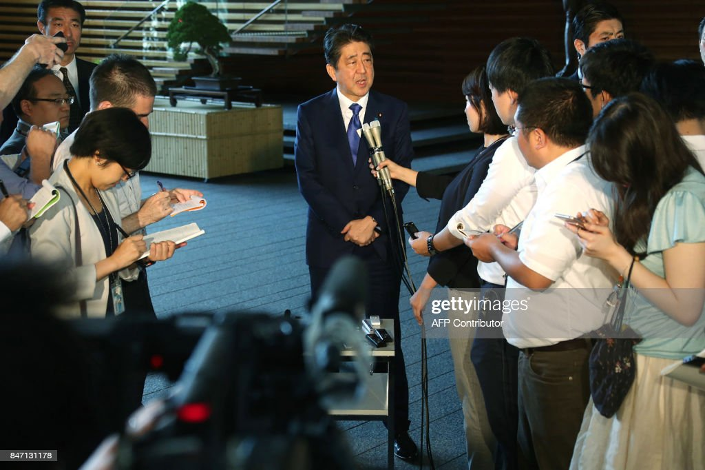 Japan's Prime Minister Shinzo Abe (C) answers questions at his official residence in Tokyo on September 15, 2017. North Korea fired a ballistic missile over Japan and into the Pacific on September 15, responding to new UN sanctions with what appeared to be its furthest-ever missile flight amid high tensions over its weapons programmes. / AFP PHOTO / JIJI PRESS / STR / Japan OUT