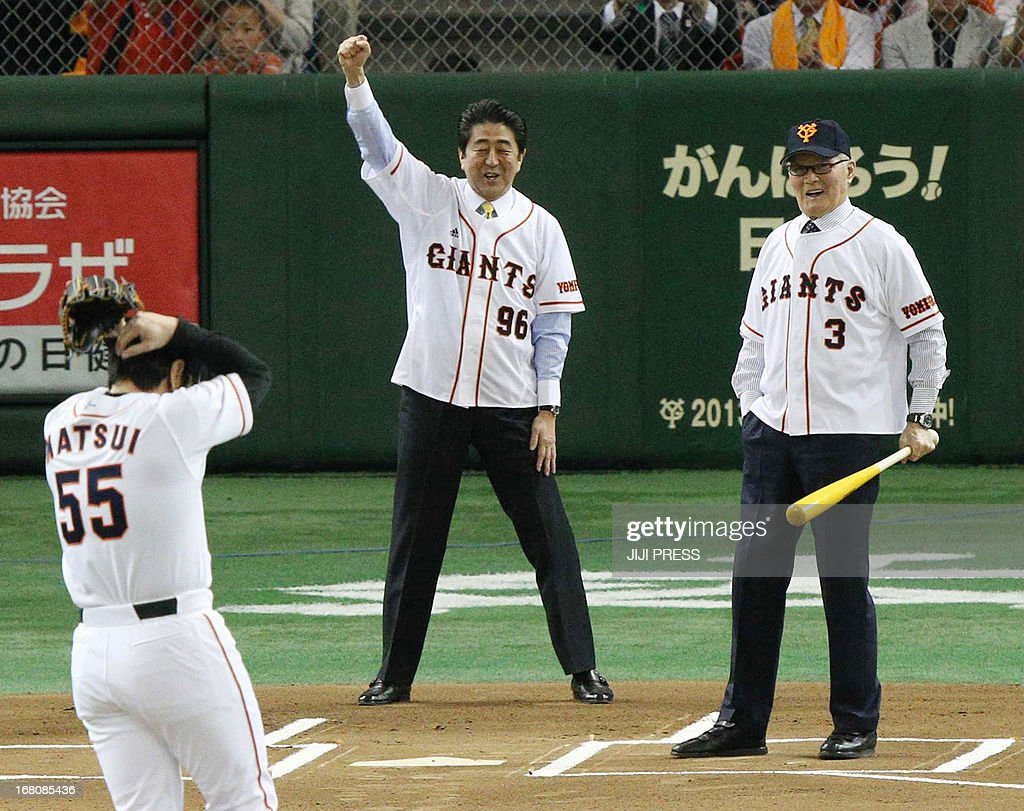 Japan's Prime Minister Shinzo Abe (C) calls a strike after former Yomiuri Giants and New York Yankees slugger Hideki Matsui (L) threw the ball while Japanese legendary slugger Shigeo Nagashima (R) bats, during a ceremony to receive the 'People's Honour Award' at the Tokyo Dome on May 5, 2013. Nagashima, 77, venerated in Japan as a national hero, played and managed the Yomiuri Giants. JAPAN OUT AFP PHOTO / JIJI PRESS