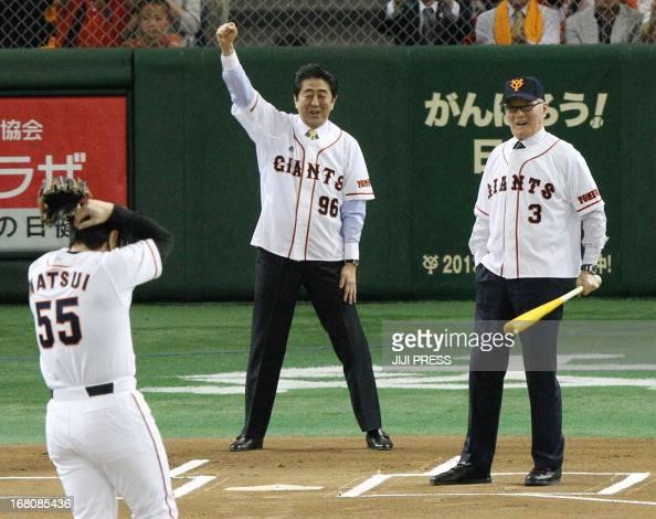 Japan's Prime Minister Shinzo Abe calls a strike after former Yomiuri Giants and New York Yankees slugger Hideki Matsui threw the ball while Japanese...