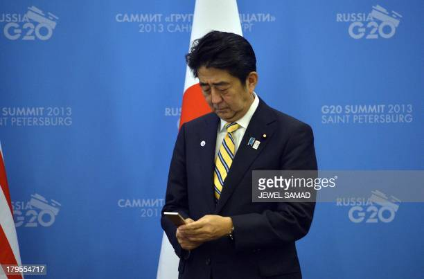 Japans Prime Minister Shinzo Abe checks his cell phone as he waits for US President Barack Obama to arrive for a bilateral meeting on the sideline of...