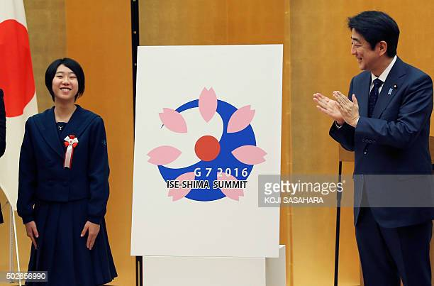 Japan's Prime Minister Shinzo Abe claps as high school student Shiho Utsumiya who designed the logo for the IseShima G7 Summit smiles during its...