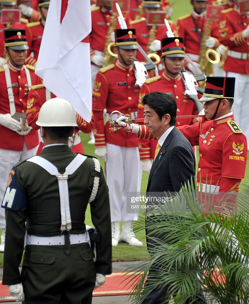 Japan's Prime Minister Shinzo Abe (C) inspects a presidential honour guard upon his arrival at the Presidential Palace in Jakarta on January 18, 2013. Abe met Indonesia's President Susilo Bambang Yudhoyono but has cut short his trip to fly home on January 19 and deal with the hostage crisis in Algeria in which numerous Japanese are caught up. AFP PHOTO / Bay ISMOYO