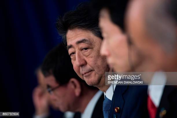 Japan's Prime Minister Shinzo Abe listens to a statement before luncheon with US Korean and Japanese leaders at the Palace Hotel during the 72nd...