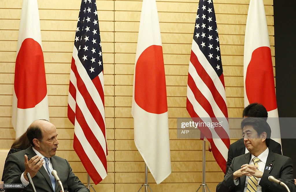 Japan's Prime Minister Shinzo Abe (R) listens to US ambassador to Japan John Roos (L) at they attend their joint announcement on a US-Japan agreement on the return of some of the US bases in Okinawa, at Abe's official residence in Tokyo April 5, 2013. Japan and the United States agreed on a plan that will see some land occupied by the US military returned to the islands in a bid to break the deadlock in a long-stalled deal. AFP PHOTO / POOL / Issei KATO