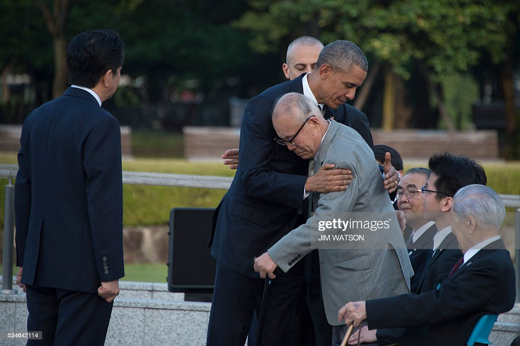 Japan's Prime Minister Shinzo Abe (L) looks on as US President Barack Obama (centre L) hugs a survivor (centre R) of the 1945 atomic bombing of Hiroshima, during a visit to the Hiroshima Peace Memorial Park on May 27, 2016. Obama on May 27 paid moving tribute to victims of the world's first nuclear attack. / AFP / Jim Watson