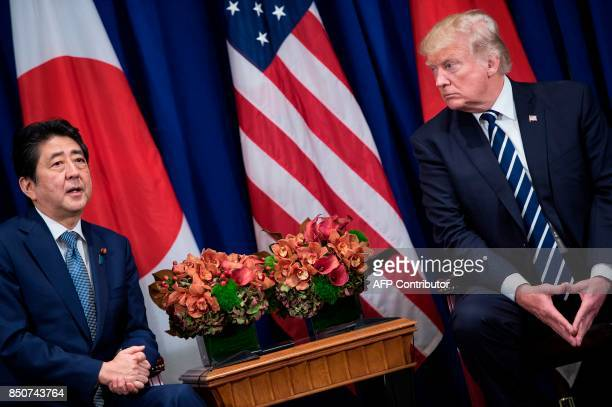 Japan's Prime Minister Shinzo Abe makes a statement for the press while US President Donald Trump listens before a meeting at the Palace Hotel during...