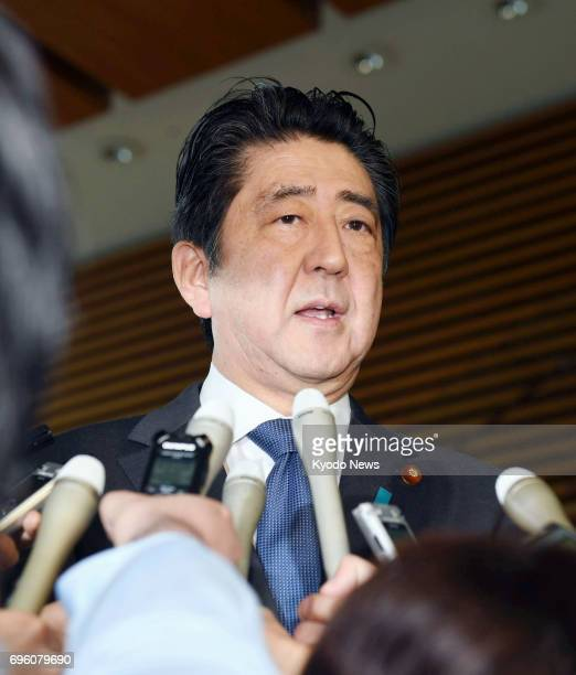 Japan's Prime Minister Shinzo Abe meets with reporters on June 15 after the parliament enacted contentious legislation to criminalize the planning of...