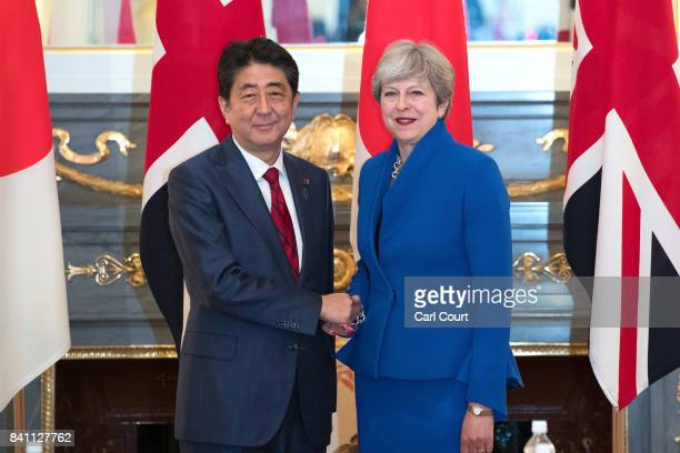 Japan's Prime Minister Shinzo Abe shakes hands with Britain's Prime Minister Theresa May during a bilateral meeting on August 31 2017 in Tokyo Japan...