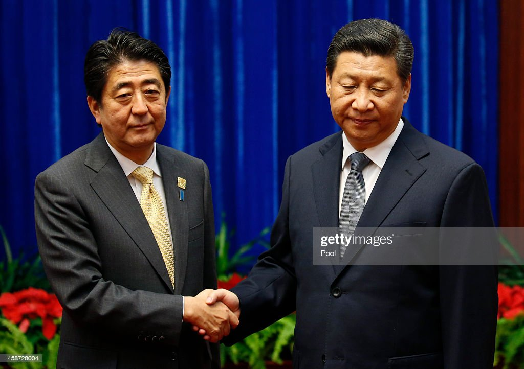 Japan's Prime Minister Shinzo Abe shakes hands with China's President Xi Jinping (R), during their meeting at the Great Hall of the People, on the sidelines of the Asia Pacific Economic Cooperation (APEC) meetings, November 10, 2014 in Beijing, China. APEC Economic Leaders' Meetings and APEC summit is being held at Beijing's outskirt Yanqi Lake.