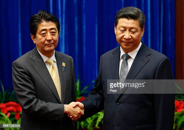 Japan's Prime Minister Shinzo Abe shakes hands with China's President Xi Jinping during their meeting at the Great Hall of the People on the...