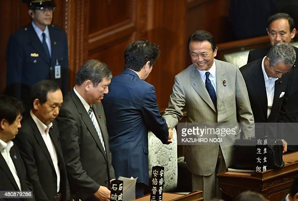Japan's Prime Minister Shinzo Abe shakes hands with Deputy Prime Minister and Finance Minister Taro Aso after controversial security bills passed...