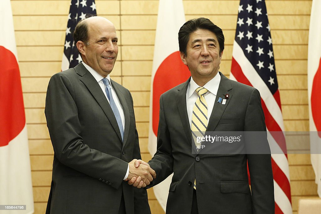 Japan's Prime Minister Shinzo Abe (R) shakes hands with US ambassador to Japan John Roos (L) at their joint announcement on a US-Japan agreement on the return of some of the US bases in Okinawa, at Abe's official residence in Tokyo April 5, 2013. Japan and the United States agreed on a plan that will see some land occupied by the US military returned to the islands in a bid to break the deadlock in a long-stalled deal. AFP PHOTO / POOL / Issei KATO
