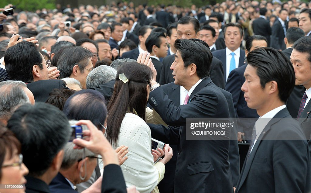 Japan's Prime Minister Shinzo Abe (C) shakes hands with wellwishers during a garden party to admire cherry blossoms hosted by Abe in Tokyo on April 20, 2013. Several thousands of people were invited to the annual spring garden party.