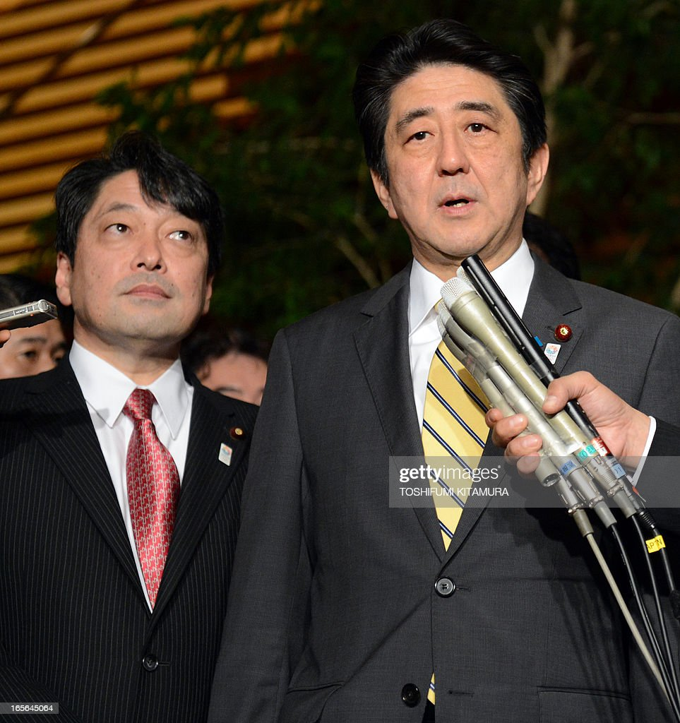 Japan's Prime Minister Shinzo Abe (R) speaks to the media beside Japanese Defence Minister Itsunori Onodera (L) at his official residence in Tokyo on April 5, 2013 after attending a US-Japan joint announcement. Japan and the United States agreed on a plan that will see some land occupied by the US military returned to the islands in a bid to break the deadlock in a long-stalled deal. AFP PHOTO / TOSHIFUMI KITAMURA