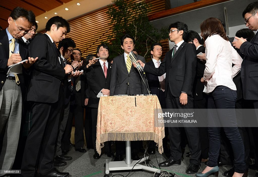 Japan's Prime Minister Shinzo Abe (C) speaks to the media beside Japanese Defence Minister Itsunori Onodera (7th L) at his official residence in Tokyo on April 5, 2013 after attending a US-Japan joint announcement. Japan and the United States agreed on a plan that will see some land occupied by the US military returned to the islands in a bid to break the deadlock in a long-stalled deal.