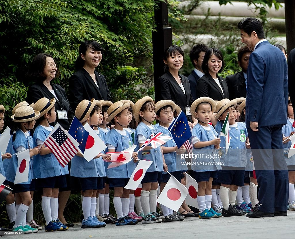 Japan's Prime Minister Shinzo Abe (R) talks with schoolchildren waiting for the arrival of world leaders at Ise-Jingu Shrine in the city of Ise in Mie prefecture, on May 26, 2016 on the first day of the G7 leaders summit. World leaders kick off two days of G7 talks in Japan on May 26 with the creaky global economy, terrorism, refugees, China's controversial maritime claims, and a possible Brexit headlining their packed agenda. / AFP / MANAN