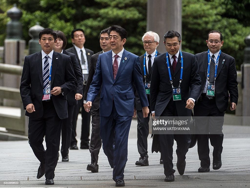 Japan's Prime Minister Shinzo Abe (C) walks in the courtyard outside Ise-Jingu Shrine in the city of Ise in Mie prefecture, on May 26, 2016 on the first day of the G7 leaders summit. World leaders kick off two days of G7 talks in Japan on May 26 with the creaky global economy, terrorism, refugees, China's controversial maritime claims, and a possible Brexit headlining their packed agenda. / AFP / MANAN