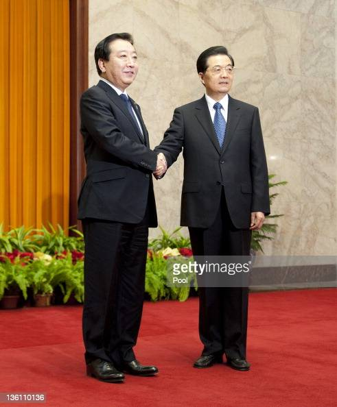 Japan's Prime Minister Yoshihiko Noda shakes hands with China's President Hu Jintao at the Great Hall of the People on December 26 2011 in Beijing...