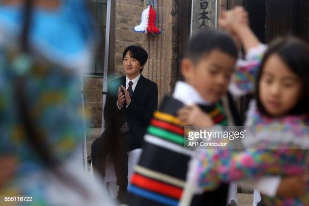 Japan's Prince Akishino and his wife Princess Kiko enjoy a performance during a visit to a Japanese school in Santiago on September 28 2017 / AFP...