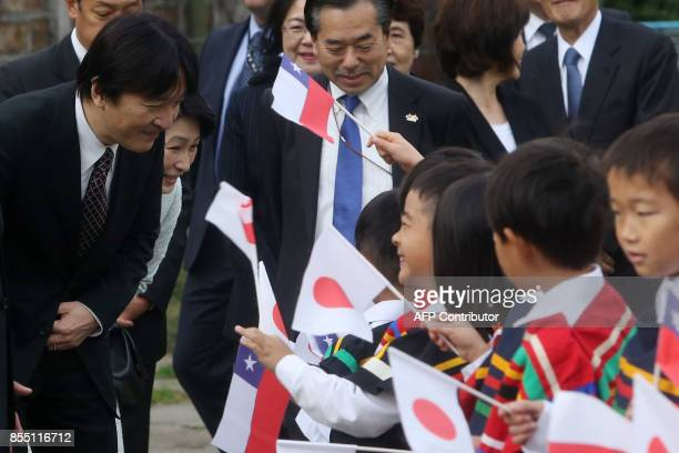 Japan's Prince Akishino and his wife Princess Kiko greet children during a visit to a Japanese school in Santiago on September 28 2017 / AFP PHOTO /...