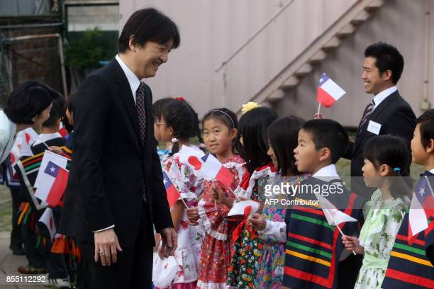 Japan's Prince Akishino greets children during a visit to a Japanese school in Santiago on September 28 2017 / AFP PHOTO / CLAUDIO REYES