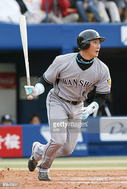 Japan's professional baseball Hanshin Tigers outfielder Tomoaki Kanemoto hits a single against Bay Stars to mark his 2000th career hits at the...