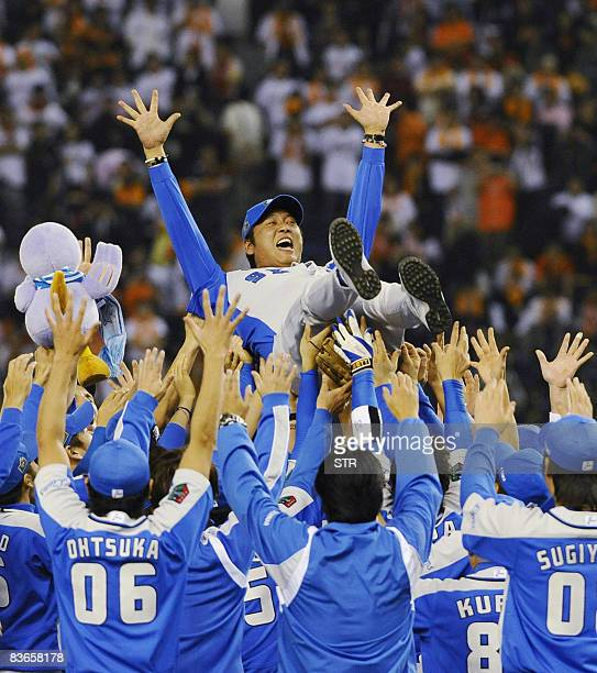 Japan's professional baseball Pacific League champion team Seibu Lions members toss up their manager Hisanobu Watanabe in the air as they defeated...
