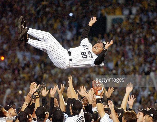 Japan's professional baseball team Hanshin Tigers manager Akinobu Okada is tossed in the air by players to celebrate their victory in the Central...