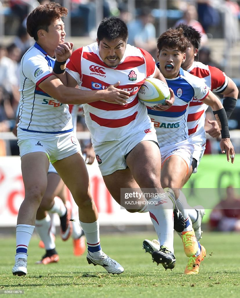 Japan's Prop Yu Chinen (C) runs with the ball against South Korea's full-back Nam Young Soo (L) during their Asian Rugby Championship rugby match in Yokohama on April 30, 2016. / AFP / KAZUHIRO