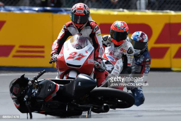 TOPSHOT Japan's rider Kaito Toba on his Honda Team Asia N°27 is about to crash with the motorcycle of Italy's rider Manuel Pagliani during a Moto3...