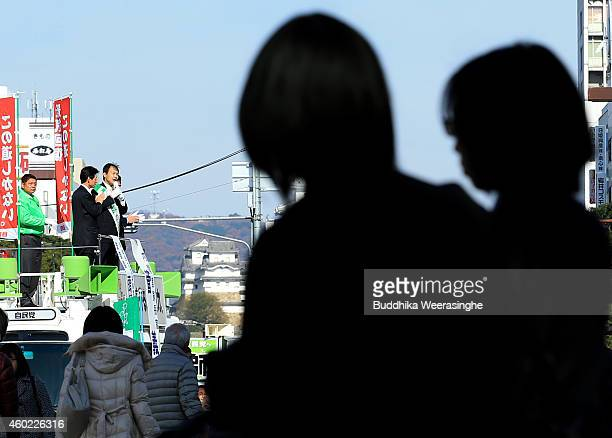 Japan's ruling Liberal Democratic Party candidate Nobuhide Zushi speaks to voters from the roof of a campaign bus during his party election campaign...