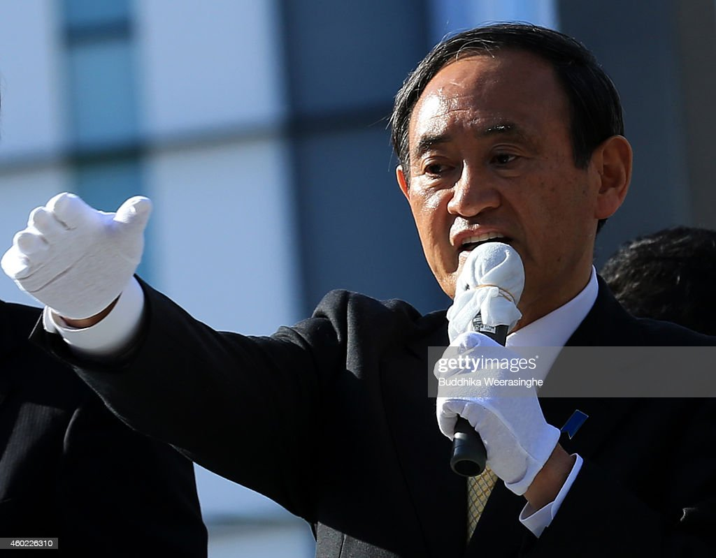 Japan's ruling Liberal Democratic Party (LDP) Chief Cabinet Secretary <a gi-track='captionPersonalityLinkClicked' href=/galleries/search?phrase=Yoshihide+Suga&family=editorial&specificpeople=3868279 ng-click='$event.stopPropagation()'>Yoshihide Suga</a> speaks to voters from the roof of a campaign bus during his party election campaign rally on December 10, 2014 in Himeji, Japan. The focal points of the election on December 14 are economic programs, the postponement of a consumption tax hike, a re-interpretation of the constitution on collective self-defense, and the future of nuclear energy.