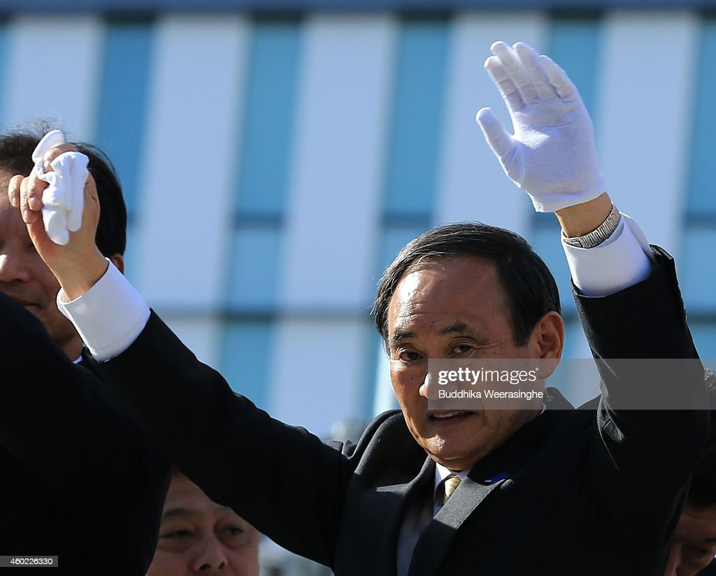 Japan's ruling Liberal Democratic Party (LDP) Chief Cabinet Secretary <a gi-track='captionPersonalityLinkClicked' href=/galleries/search?phrase=Yoshihide+Suga&family=editorial&specificpeople=3868279 ng-click='$event.stopPropagation()'>Yoshihide Suga</a> waves to voters from the roof of a campaign bus during his party election campaign rally on December 10, 2014 in Himeji, Japan. The focal points of the election on December 14 are economic programs, the postponement of a consumption tax hike, a re-interpretation of the constitution on collective self-defense, and the future of nuclear energy.