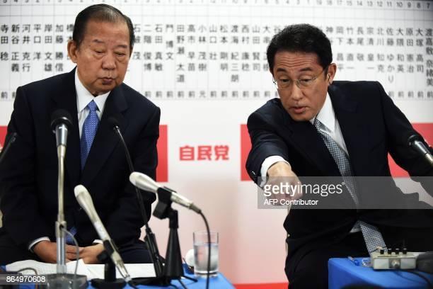 Japan's ruling Liberal Democratic party's General Secretary Toshihiro Nikai and Policy Research Council chairman Fumio Kishida watch a TV news...