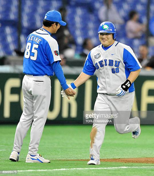 Japan's Saitama Seibu Lions slugger Takeya Nakamura is congratulated by his team's coach Masakazu Seike after his threerun homer during the second...