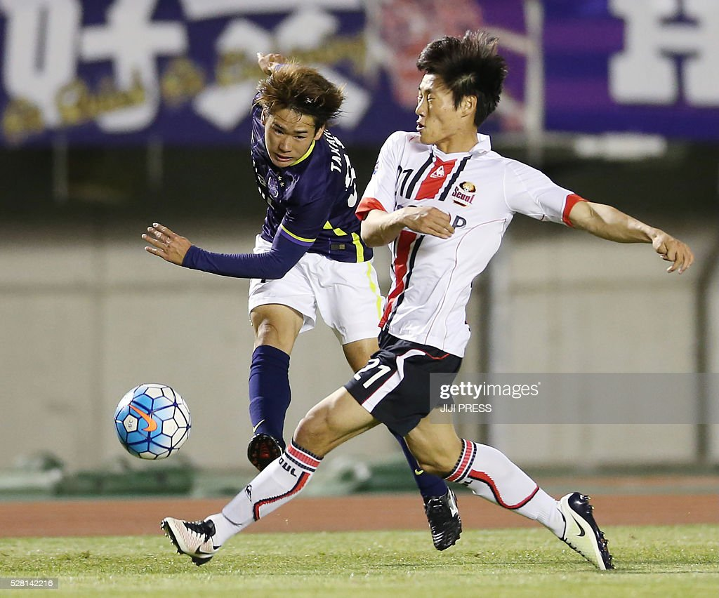 Japan's Sanfrecce Hiroshima defender Soya Takahashi (L) shoots beside South Korea's FC Seoul midfielder Sim Sangmin (R) during their AFC champions league group F football match in Hiroshima on May 4, 2016. / AFP / JIJI