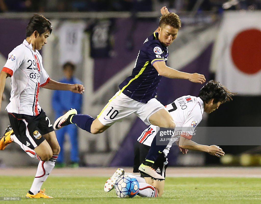Japan's Sanfrecce Hiroshima forward Takkuma Asano (C) dribbles the ball among South Korea's FC Seoul midfielder Lee Sanghyeob (L) and midfielder Kim Chi-Woo (R) during their AFC champions league group F match in Hiroshima on May 4, 2016. / AFP / JIJI PRESS / JIJI PRESS / Japan OUT