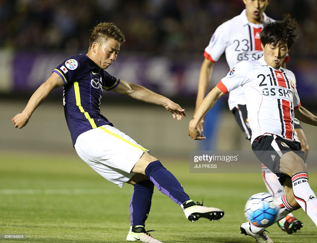Japan's Sanfrecce Hiroshima forward Takkuma Asano (L) shoots beside South Korea's FC Seoul midfielder Sim Sangmin (C) and defender Sim Wooyeon (R) during their AFC champions league group F match in Hiroshima on May 4, 2016. / AFP / JIJI PRESS / JIJI PRESS / Japan OUT