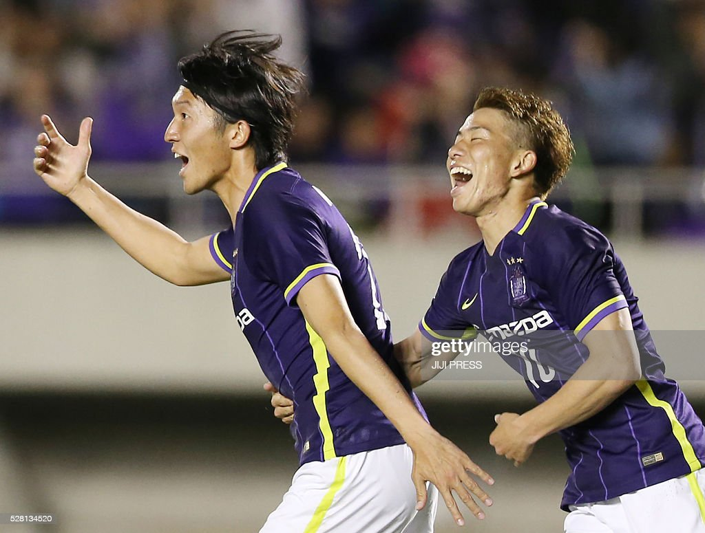 Japan's Sanfrecce Hiroshima forward Yusuke Minagawa (L) celebrates his goal with teammate Takkuma Asano (R) during their AFC champions league group F match against South Korea's FC Seoul in Hiroshima on May 4, 2016. / AFP / JIJI PRESS / JIJI PRESS / Japan OUT