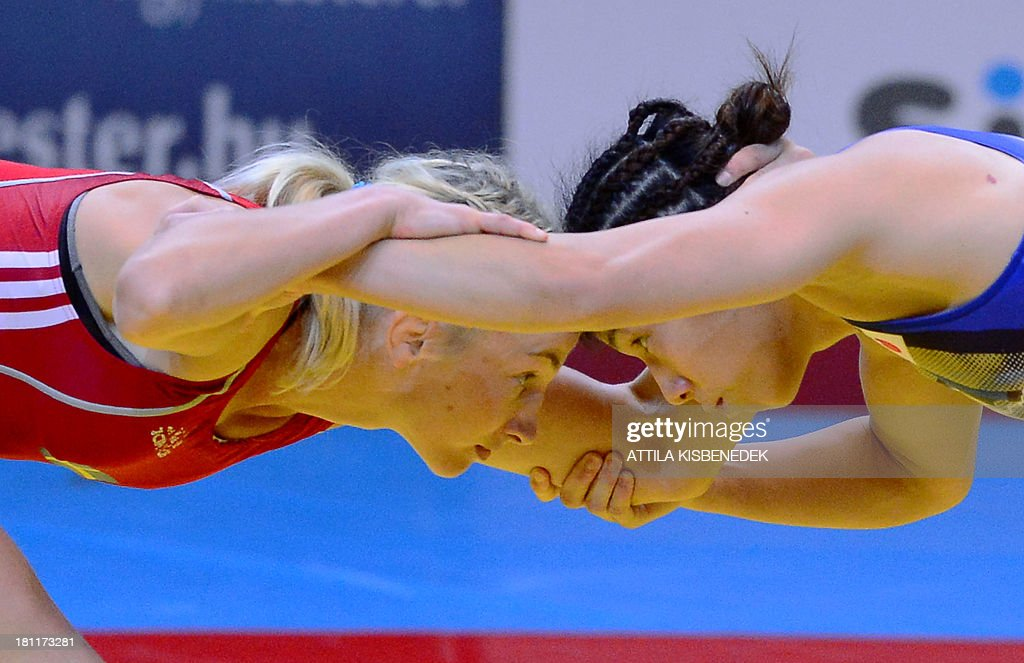Japan's Saori Yoshida (blue) and Sweden's Sofia Magdalena Mattsson (red) fight during the women's free style 55 kg category for gold of the FILA World Wrestling Championships in Budapest on September 19, 2013. Yoshida won the gold medal.