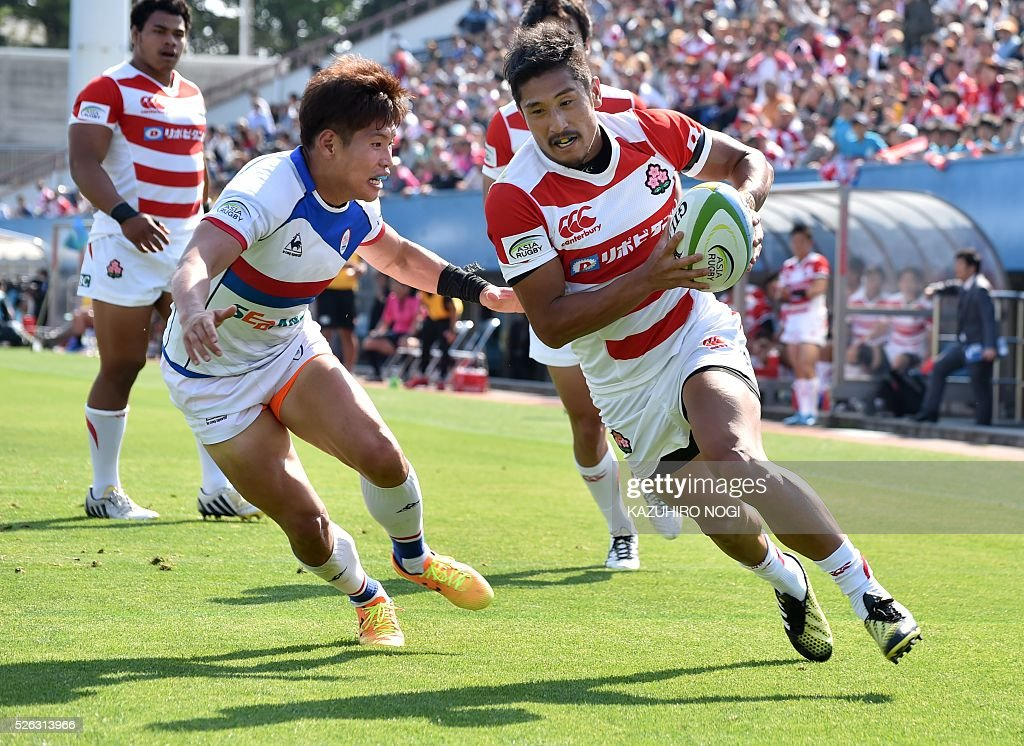Japan's scrum-half Keisuke Uchida (R) scores a try against South Korea during their Asian Rugby Championship rugby match in Yokohama on April 30, 2016. / AFP / KAZUHIRO