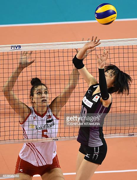 Japan's setter Haruka Miyashita tosses the ball while Kubra Akman of Turkey looks on during their women's volleyball World Grand Prix final round...