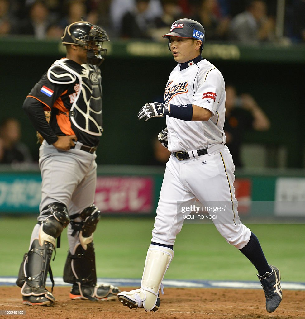 Japan's Shinnosuke Abe (R) crosses home-plate as he makes his second homer in the second inning of the second-round Pool 1 game against the Netherlands in the World Baseball Classic tournament at Tokyo Dome on March 12, 2013. At left is Netherlands' catcher Dashenko Ricardo.