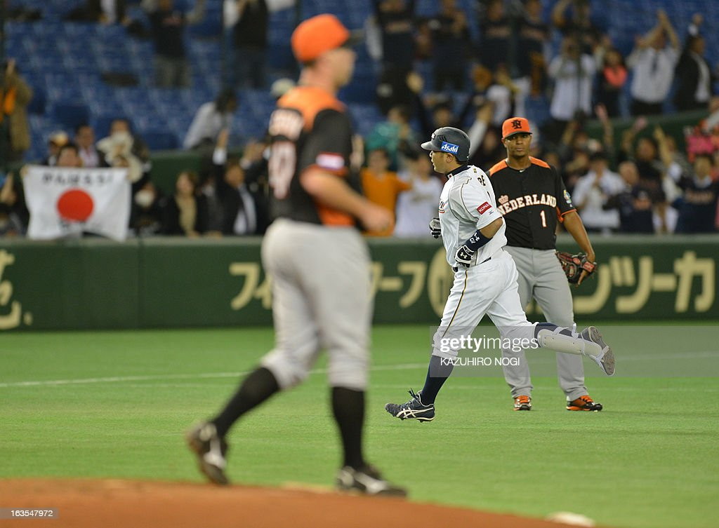 Japan's Shinnosuke Abe (2nd R) runs to home-plate past the Netherlands pitcher David Bergman (L) during the second inning of their second-round Pool 1 game in the World Baseball Classic tournament at Tokyo Dome on March 12, 2013.