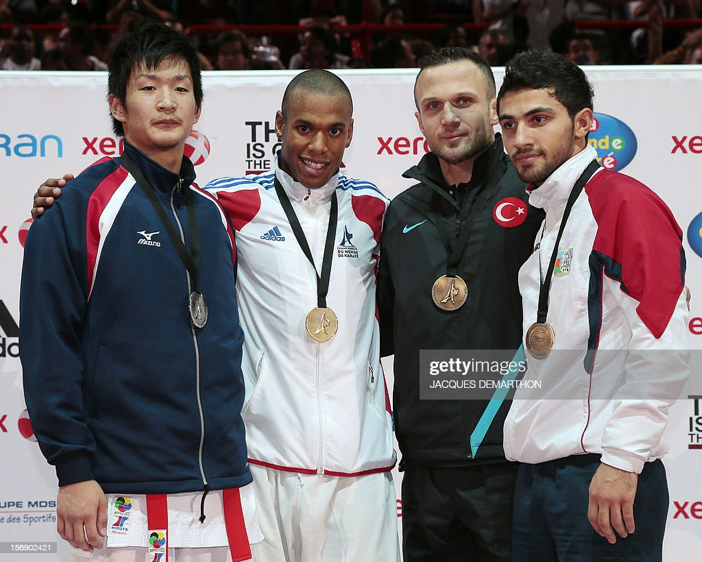 Japan's silver medalist Ryutaro Araga, French gold medalist Kenji Grillon and Turkey's bronze medalist Yavuz Karamollaoglu and Azerbaidjan's bronze Aykhan Mamayev pose on the podium of the Male Kumite under 84 Kg category at the Karate world championships on November 24, 2012 in Paris.