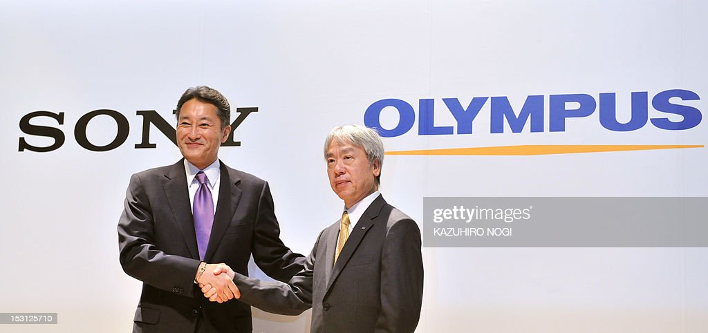 Japan's Sony Corporation President Kazuo Hirai (L) and Olympus Corporation President Hiroyuki Sasa (R) shake hands after their joint press conference in Tokyo on October 1, 2012. Olympus and Sony announced that the two companies have entered into a business alliance agreement and a capital alliance agreement through a third-party allotment of Olympus's common shares to Sony.